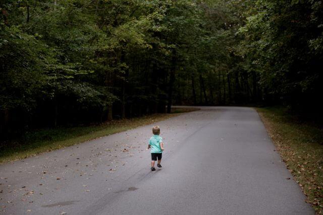 一人で道路の真ん中を歩く小さな男の子