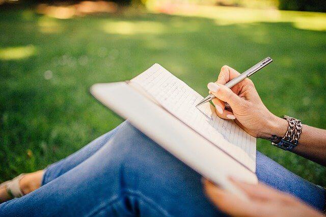 女性が芝生でノートにメモをしている