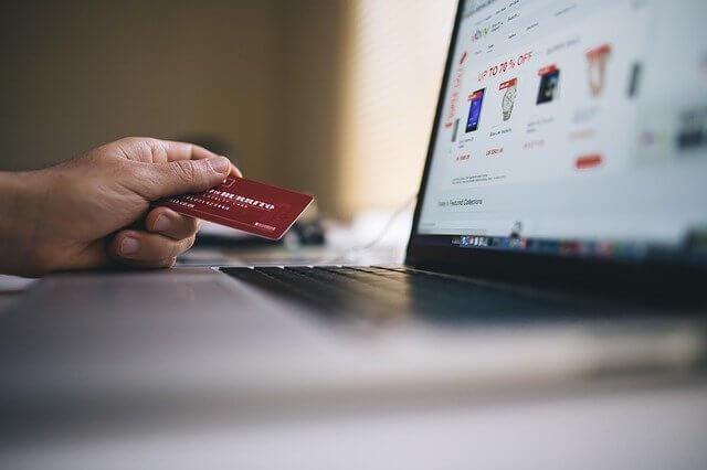 パソコンの前でクレジットカードを手にしている
