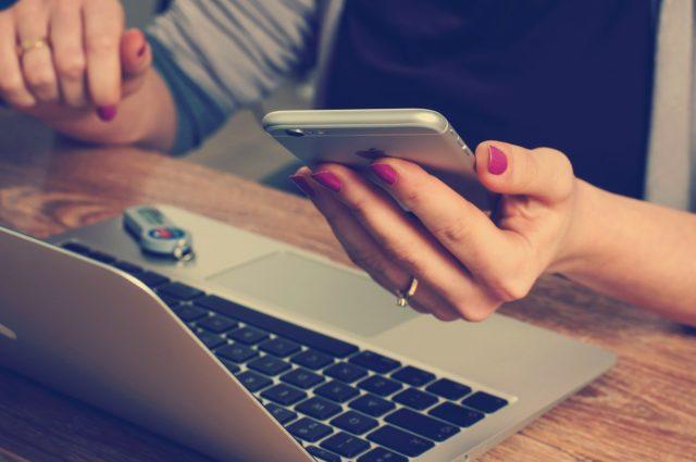パソコンの前でスマホを手に持つ女性