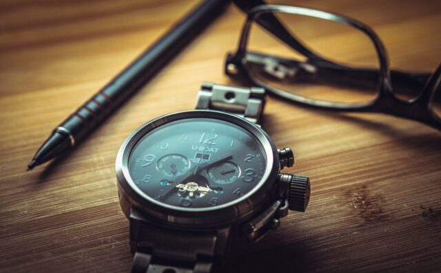 机の上に置いてある眼鏡と腕時計とペン