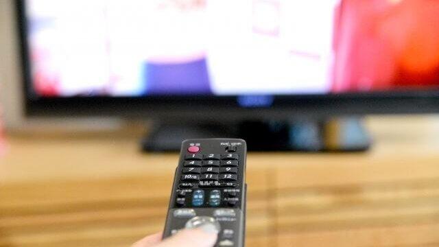 テレビに向かってチャンネル操作をする