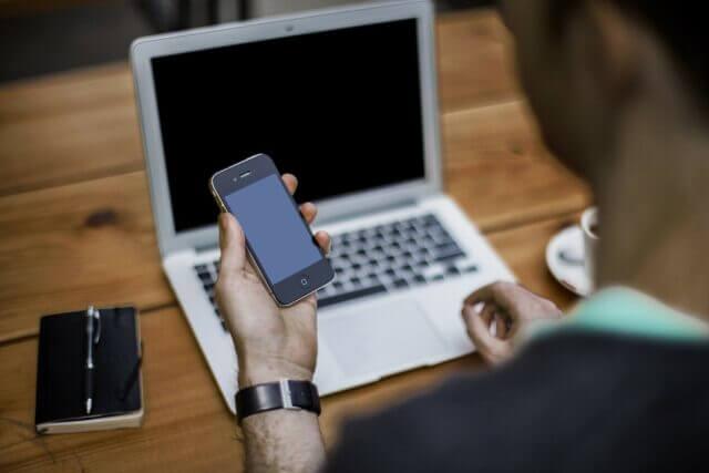 机の上にパソコンとペン付きの手帳を置いてスマートフォンをながめる男性
