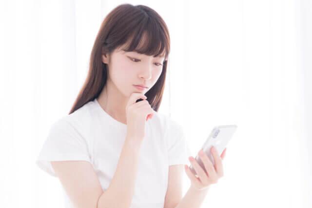 スマートフォンをみて考えるロングヘアの女性