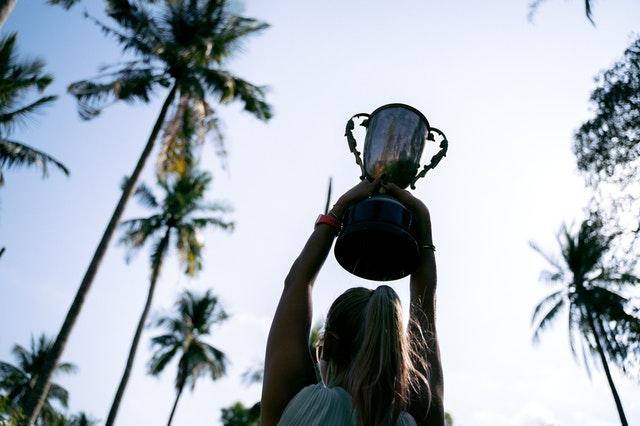 優勝カップを持ち上げる女性
