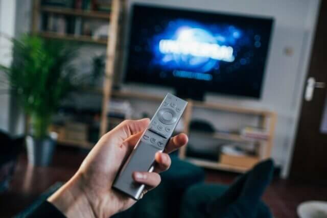 テレビに向かってチャンネル操作をする人の手