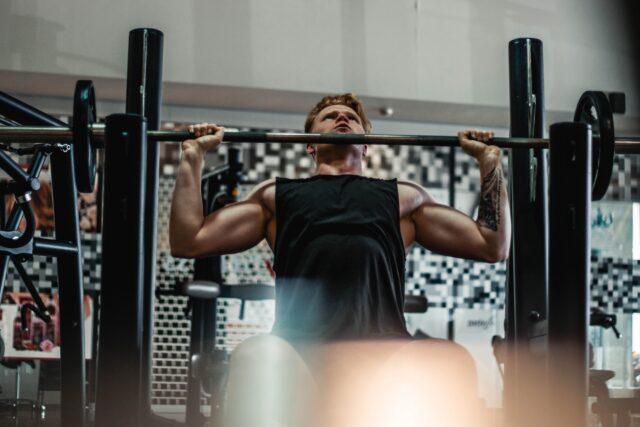 筋肉がムキムキの人がベンチプレスをあげてトレーニングをしている
