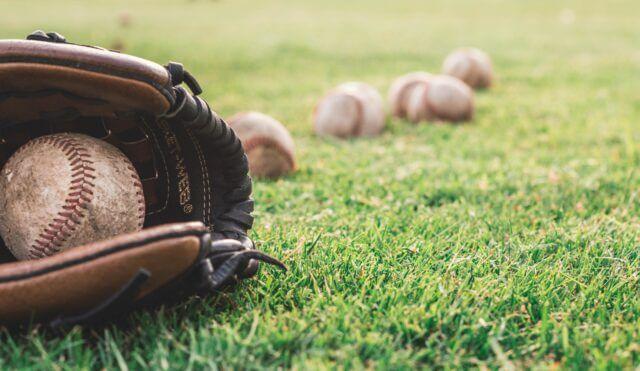 芝生の上にボールをはさんだままのグローブと野球のボールが転がっている