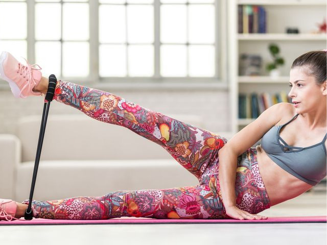 脚にバンドをつけてトレーニングをしている女性