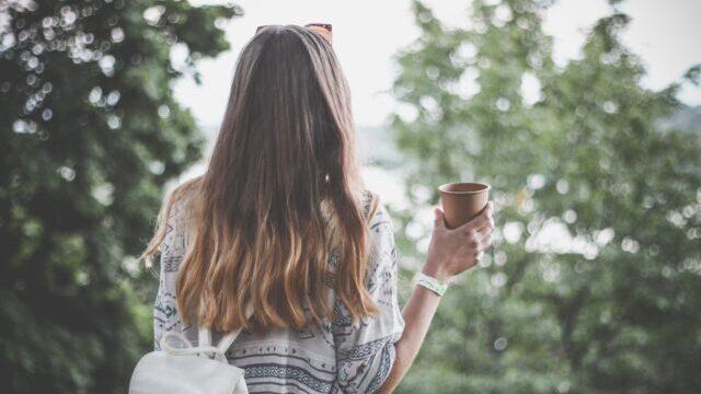 後ろ姿の美女がコップを片手に木々を眺めている