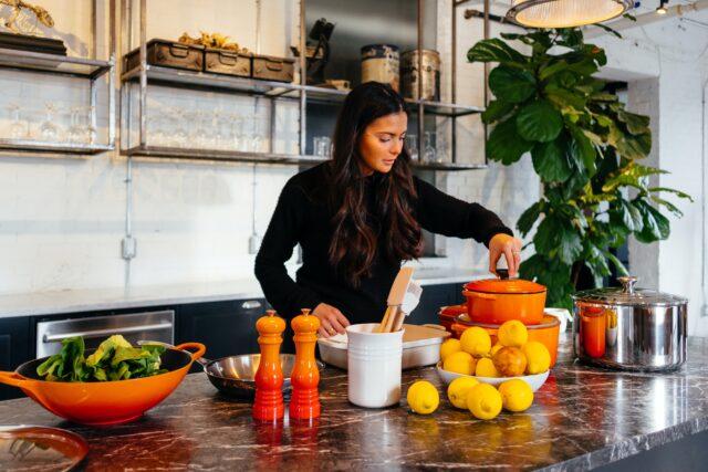 フルーツや調味料を並べキッチンで料理をしている女性