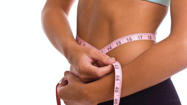 お腹がくびれている人がメジャーでサイズを測っている